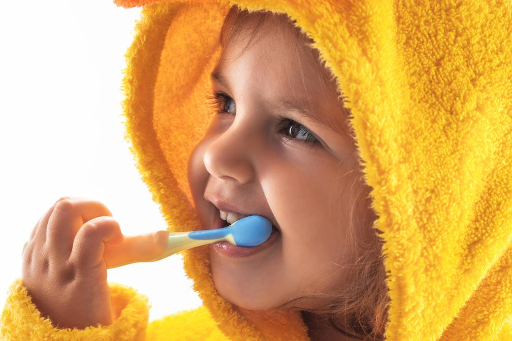 blonde-haired child wearing a yellow fuzzy hoodie brushing her teeth with a blue and yellow toothbrush and smiling