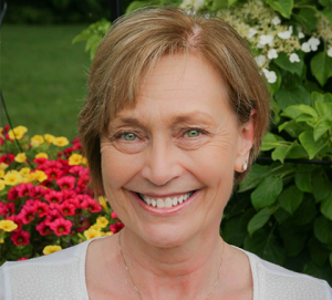 photograph of dental hygienist Mary Nienhouse smiling in front of colorful flowers and a green bush