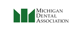 logo for the michigan dental association green on a white background