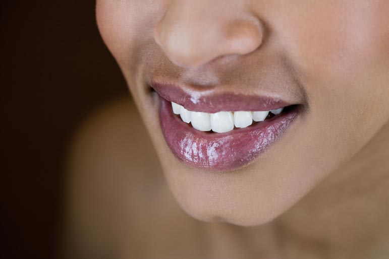 a dark-skinned woman smiles showing off her white teeth