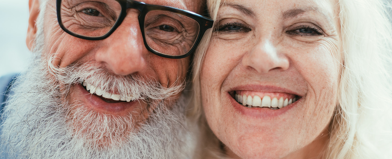 older couple of a man with dark-rimmed eyeglasses, a mustache, and a beard next to a woman with light hair smiling