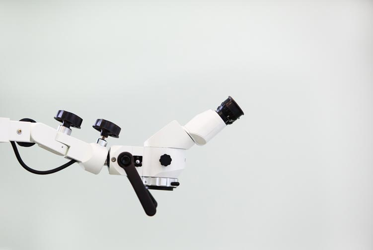 photograph of a white microscope against a white background