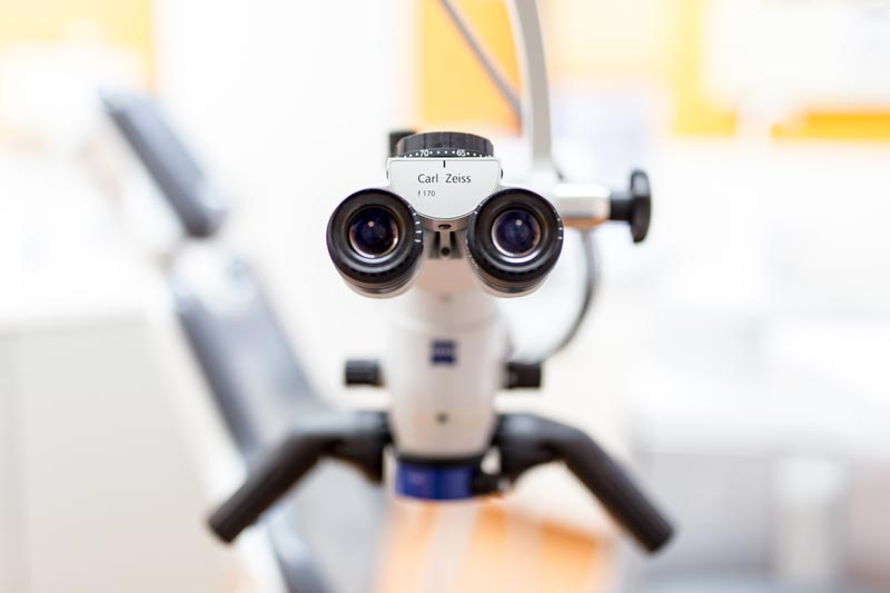 photograph of the eyepiece of a microscope in front of a dental chair