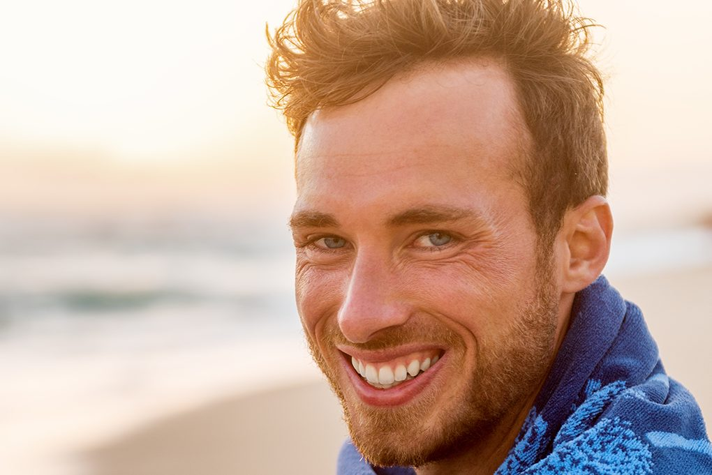 man on the beach smiling widely with the sun shining in the background
